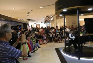 A young participant from the Nanyang Academy of Fine Arts' School of Young Talents drawing the crowd at ION Orchard in the evening - Picture by Steinway Gallery Singapore