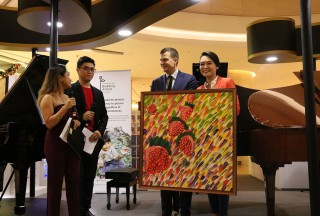 Adam Gyorgy (L) receiving a painting by one of the beneficiaries from The Business Times Budding Artists Fund, from Celine Goh, General Manager of Steinway Gallery Singapore (R) - Picture by Steinway Gallery Singapore