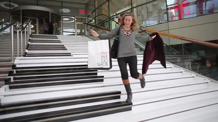 Excited lady walking down piano stairs