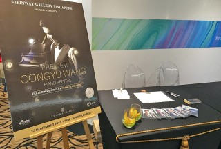 Poster of Congyu Wang's Piano Recital, next to copies of his new CD, Charme