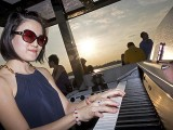 Pianovers Sailaway 2016, Julia Goh playing the piano, with a sunset backdrop