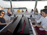 Pianovers Sailaway 2016, Julia Goh, and Gregory Goh playing the piano on the flybridge
