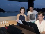 Pianovers Sailaway 2016, Julia, Xi Kun, and Chris at the piano on the flybridge