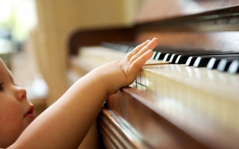 Closeup of a baby playing the piano